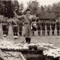Sgt Major George Greenway saluting over the grave of Pte Thompson. Oct 1957.